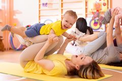 Yoga for babies. Child-friendly fitness for women with toddlers. Lifestyle concept of parent activity with kids. Yoga for babies. Child-friendly fitness for royalty free stock photography