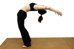 Yoga backbend. Woman practicing yoga and making back-bend on a brown floor, isolated with clipping path Stock Photo