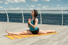 Yoga on the background of sea. Pose cross twine Stock Photos