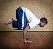 Yoga bakasana crane pose. Handsome Indian man in white shirt doing bakasana, crane pose indoors on wooden floor at grunge background Royalty Free Stock Photos