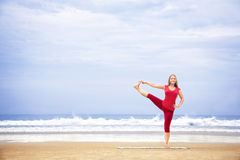 Yoga balance on one leg. Yoga utthita Hasta Padangustasana one leg balance pose by young woman with long hair in red cloth on the beach at ocean background Stock Images