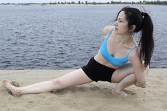 Yoga bank. Woman practising yoga stretching exercise on a sand river bank Royalty Free Stock Images