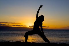 Yoga on the Beach. A woman doing yoga silhouetted in the sunset on the beach Stock Images