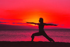 Yoga on the Beach. A woman doing yoga silhouetted in the sunset on the beach Stock Photo