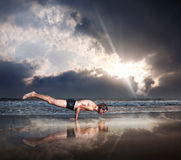 Yoga on the beach. Yoga Mayurasana peacock handstand balancing pose by fit man on the beach near the ocean at dramatic sunset sky Stock Photos