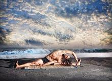 Yoga on the beach. Yoga parivrtta janu sirsasana pose by fit man with dreadlocks on the beach near the ocean at sunset background Stock Photo