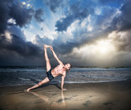 Yoga on the beach. Yoga vasisthasana side plank pose by fit man on the beach near the ocean at sunset background Stock Photo
