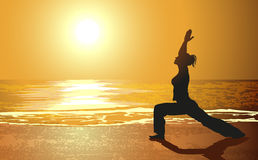 Yoga on a beach. Against sunset Stock Image