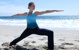 Yoga on the Beach. With her arms in warrior position Stock Photo
