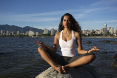 Yoga on the Beach. An attractive young Indian woman sits meditating on a rock with the ocean and city buildings in the distant background royalty free stock image