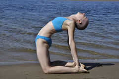 Yoga beach camel. Bald woman in yoga position ustrasana, or camel, on a beach Royalty Free Stock Images