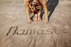 Yoga on the beach with Namaste. Woman doing yoga on the beach near Namaste handwriting in Goa, India stock photos