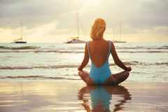 Yoga on the beach near the water in sunset Stock Photography