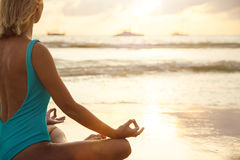 Yoga on the beach near the water in sunset Royalty Free Stock Image