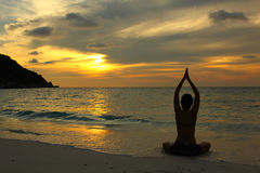Yoga on the beach. Silhouette young woman practicing yoga on the beach at sunset Stock Photos