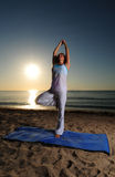 Yoga on beach with sunrise Stock Images