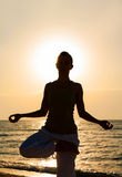 Yoga on the beach at sunrise. Stock Photography