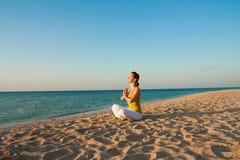 Yoga on the beach at sunrise. Stock Photo