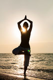 Yoga on the beach at sunrise. Royalty Free Stock Photography