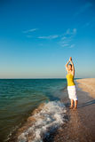 Yoga on the beach at sunrise. Stock Photos