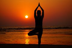 Yoga on the beach on the sunset. Young female doing yoga on the beach during sunset. Asana. Girl posing on the beach. Silhouette of the women Stock Photos