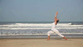 Yoga on the beach. Woman doing yoga in white costume on the beach near the ocean in Goa, India stock video footage