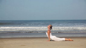 Yoga on the beach. Woman doing yoga in white costume on the beach near the ocean in Goa, India stock footage