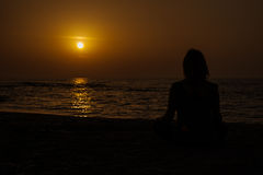 Yoga at beach. Woman at the beach in front of the sunset making yoga Stock Photos