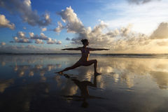Yoga on the beach. Young woman practicing yoga on the beach at sunset Stock Photos