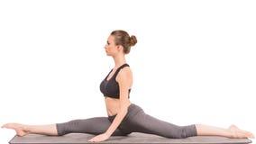 Yoga. Beautiful slim woman doing yoga exercise, sitting on the splits over white background Royalty Free Stock Image