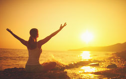 Yoga bei Sonnenuntergang auf Strand Frau, die Yoga tut Lizenzfreie Stockfotografie