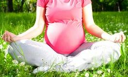 Yoga, belle femme enceinte détendant en parc Images stock