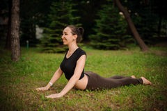 Yoga bhujangasana cobra pose by woman on green grass in the park Royalty Free Stock Images