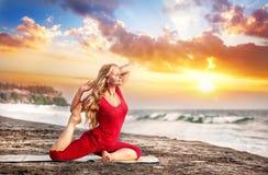 Yoga bij zonsondergangstrand stock afbeeldingen