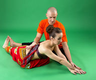 yoga Bild des Trainers hilft Frau, asana durchzuführen Lizenzfreie Stockfotos