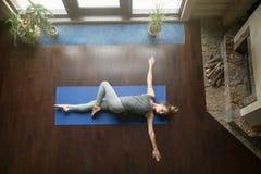 Yoga a casa: Posa girata dell'addome Fotografia Stock Libera da Diritti