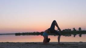 Yoga cerca del agua en la puesta del sol almacen de video