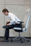 Yoga on chair in office - business man exercising Royalty Free Stock Images