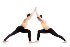 Yoga che partnering, Virabhadrasana 1 posa immagine stock libera da diritti