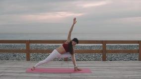 Yoga che posa sulla spiaggia di mattina archivi video
