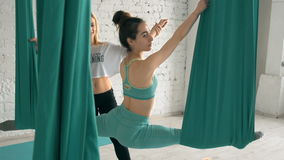 Yoga Choach Helps Female Student To Stretch Legs And Do Splits On Aerial Silks