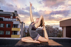 Yoga and the city. Girl, holding a yoga asana, at a rooftop in Sofia,Bulgaria Stock Photos