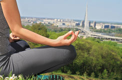 Yoga in the city : Woman meditating in yoga position in nature / park with city view close up. Stock Images