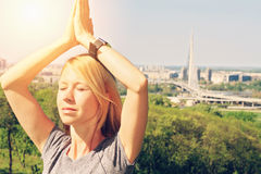 Yoga in the city : Woman meditating in yoga position in nature / Stock Photography