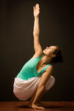 Yoga class. Young woman - yoga instructor doing yoga.Dark background royalty free stock image