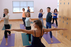 Yoga Class. Yoga instructor leading class in warrior pose Stock Images