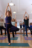 Yoga Class. Yoga instructor leading class in reaching pose wide crop Stock Photo