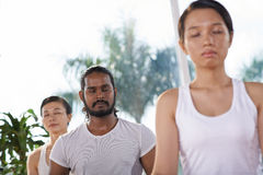 Yoga class. Asian people having class of yoga, focus on Indian man Stock Photography