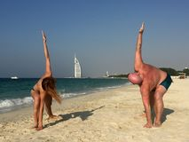 Yoga class on the beach. Father and daughter. stock image