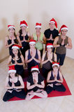 Yoga class celebrating Christmas. Yoga class group celebrating Christmas, wearing red Santa hats stock images